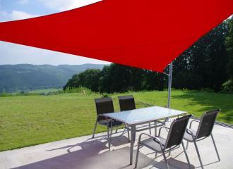 Červený trojuhelník u rodinného domu v otevřené krajině.