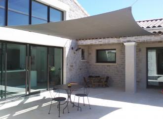 Kvalitní stín na terase u rodinného domku zajistí obdélníková plachta.