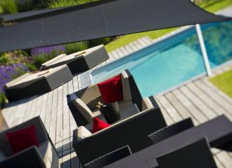 Plachta stínící posezení u bazénu.