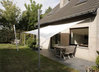 Obdélníková stínící plachta na terase u tradičního rodinného domu.