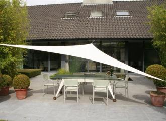 Trojuhelníková plachta na terase u rodinného domu.